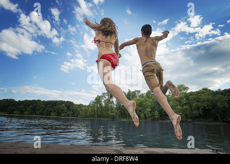 New York state USA boy and girl leaping off jetty into lake river - Stockfoto