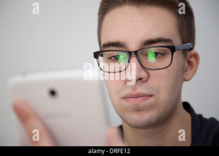 Good looking young man wearing glasses, slight reflection. Holding a white digital tablet. Serious expression. - Stock Photo