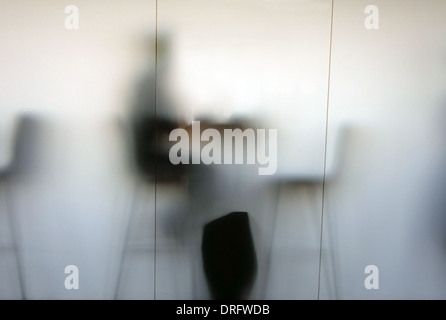 Person in cafe silhouetted behind frosted glass window, London - Stock Photo