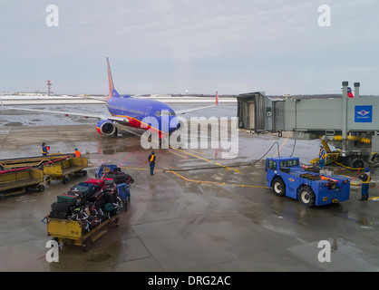Passenger airplane being serviced at airport gate between flights on rainy day - Stock Photo