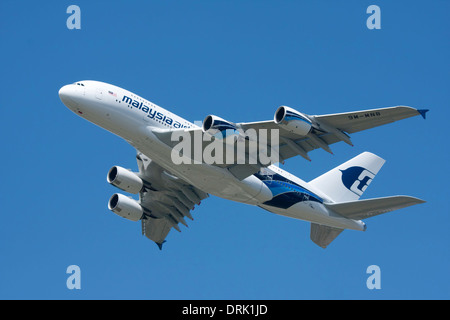airbus a380 'jet plane' from malaysia airways taking off from farnborough airshow 2012 taken against clear blue - Stock Photo