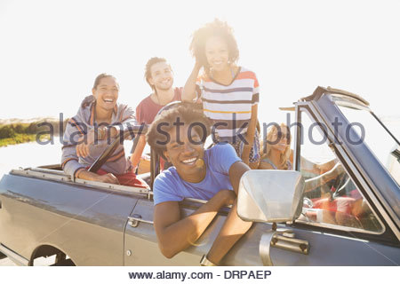 Portrait of cheerful friends on road trip - Stock Photo
