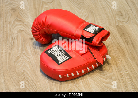 A pair of boxing gloves on the floor of a gymnasium - Stock Photo