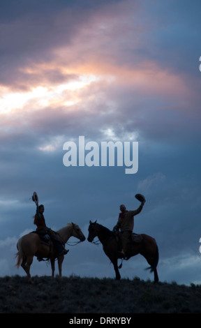 Two wranglers in silhouette raise hats after a successful horse round-up in the Bighorn Mountains of Wyoming - Stockfoto