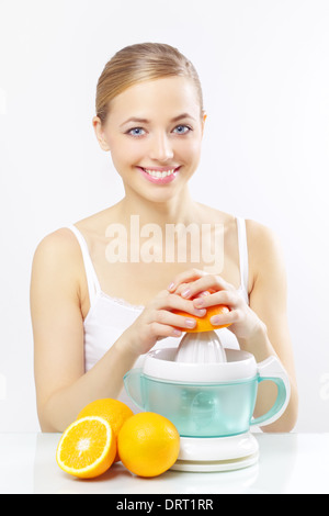 Girl with a juicer and oranges on a gray - Stock Photo