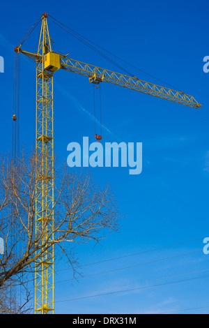 Tower crane against blue sky background - Stock Photo