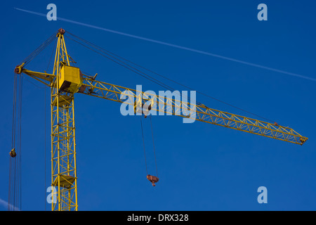 Top of tower crane against blue sky background with jet trace - Stock Photo
