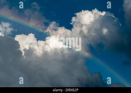 Rainbow on blue sky with white clouds - Stock Photo