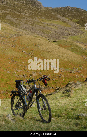 A mountain bike standing its pedal against a stone in Ennerdale valley, near Black Sail Hut in the Lake District, - Stock Photo