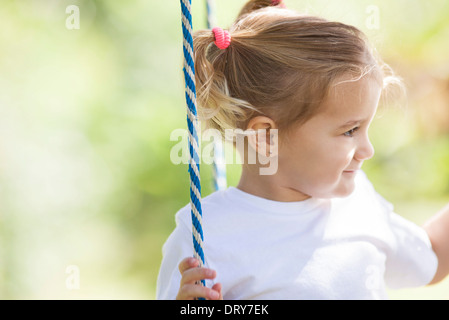 Little girl playing outdoors - Stock Photo