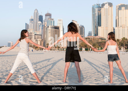 Mother and daughters holding hands at the beach, rear view - Stock Photo