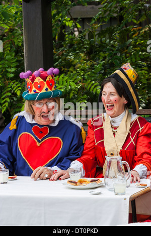 Man and woman performing outdoors as the king & queen of hearts in the mad hatters tea party - Stock Photo