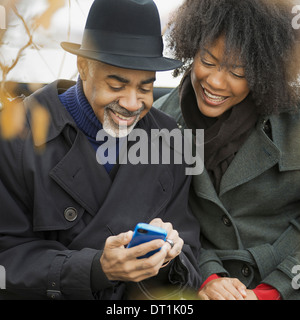Two people a man and woman standing side by side keeping in contact using mobile phones - Stock Photo