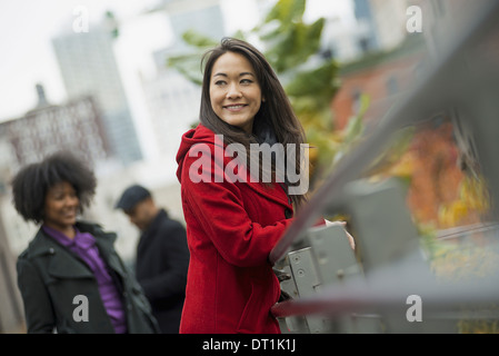 A woman in a red winter coat leaning on a railing Two people in the background City landscape of buildings - Stock Photo