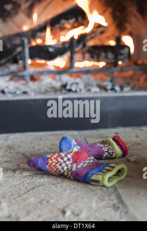 A log fire in a hearth with glowing heart and flames Patterned knitted woollen gloves - Stock Photo
