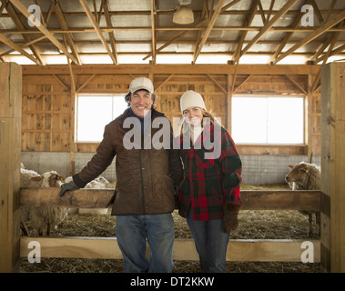 An Organic Farm in Winter in Cold Spring New York State A farmer and a woman standing by a pen full of sheep - Stock Photo