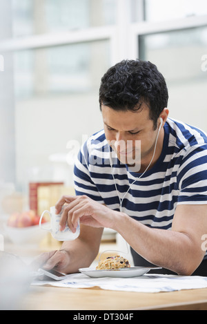 An office or apartment interior in New York City A man in a striped tee shirt leaning on the breakfast bar - Stock Photo