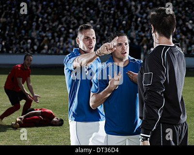 Soccer players arguing with referee on field - Stock Photo