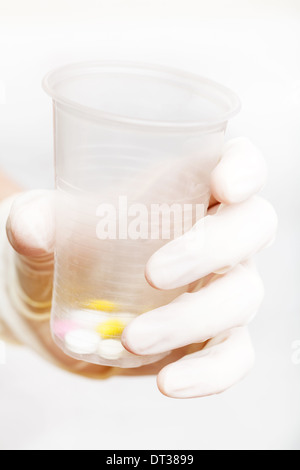 gloved hand holding plastic cup with pills on white background - Stockfoto