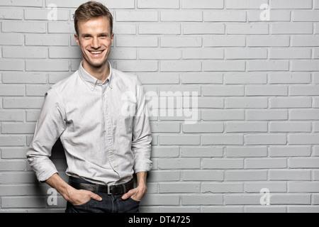Male casual portrait smiling studio brick looking camera - Stock Photo