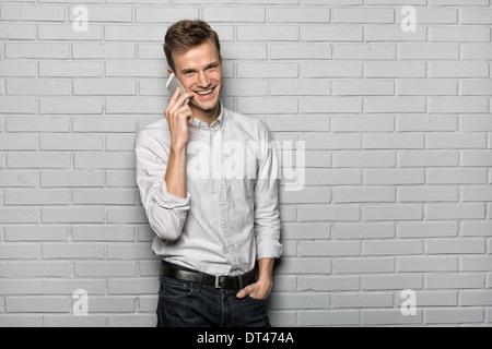 Male portrait smiling Mobile Phone studio brick looking camera - Stock Photo