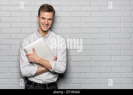 Male portrait smiling computer studio brick looking camera - Stock Photo