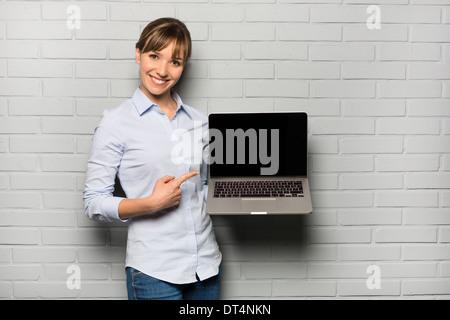 Female pretty cheerful pointing computer studio - Stock Photo