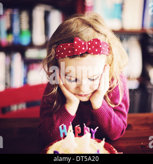 Little girl with head in hands looking bored - Stock Photo
