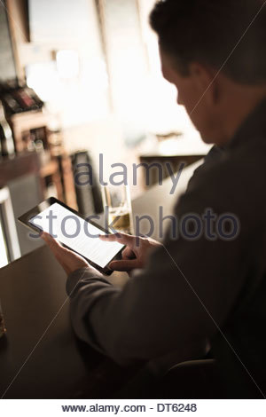 Businessmen looking at digital in a bar - Stock Photo