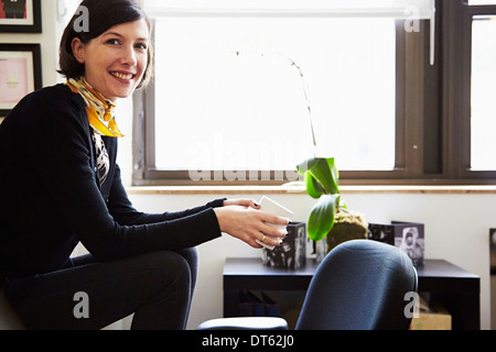 Businesswoman sitting in office - Stock Photo