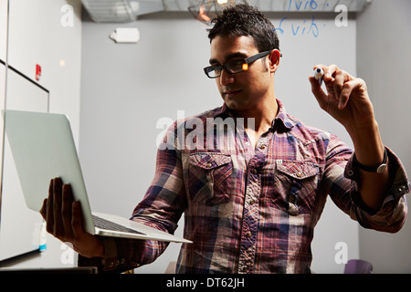 Man looking at laptop with pen in hand - Stockfoto