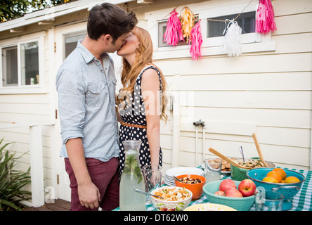 Young couple sharing a kiss in garden - Stock Photo