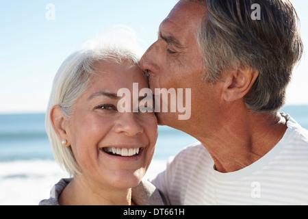 Man kissing woman on forehead - Stock Photo
