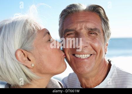 Woman pecking man on cheek - Stock Photo