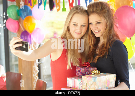 Two teenage girls taking selfie at birthday party - Stock Photo