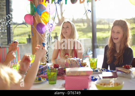 Four teenage girls celebrating with bubbles at birthday party - Stock Photo