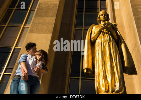 Young couple sharing a kiss next to statue, Paris, France - Stock Photo