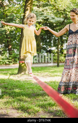 Young girl with mother walking slackline in park - Stock Photo