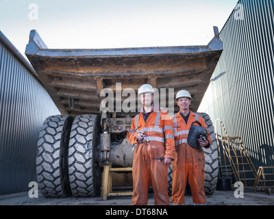 Father and son engineers in engineering workshop, portrait - Stock Photo