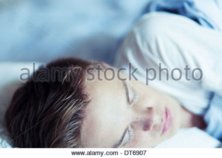 Close up of young man asleep in bed - Stock Photo
