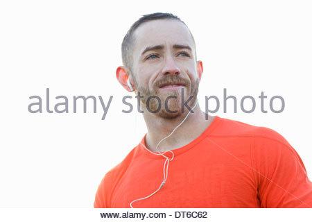 Portrait of young man wearing earphones - Stock Photo