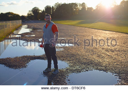 Portrait of young man standing in puddle - Stock Photo