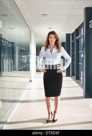 Portrait of businesswoman in corridor - Stock Photo