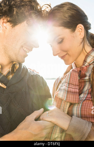 Man holding woman's hand, woman wearing engagement ring - Stock Photo