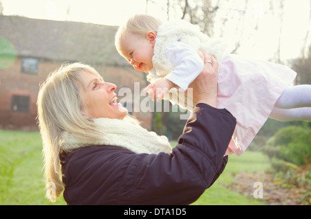 Mother Lifting Baby Daughter Outdoors - Stock Photo
