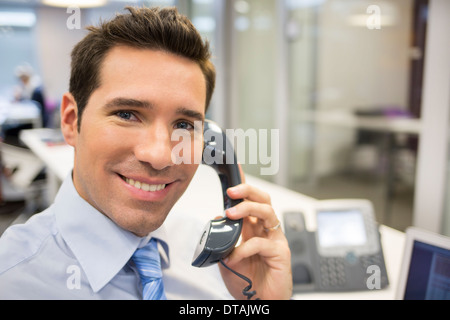 Smiling Businessman on phone in office, looking camera - Stock Photo