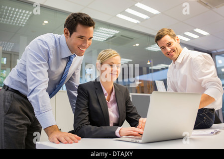 Cheerful business team working on the computer in office - Stock Photo
