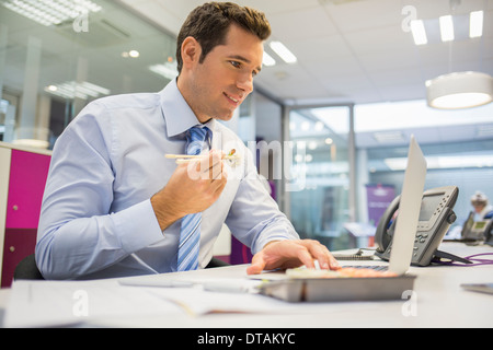 Businessman eating sushi in office - Stock Photo