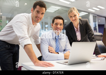 A smiling business team of three in office and planning work, looking camera - Stock Photo