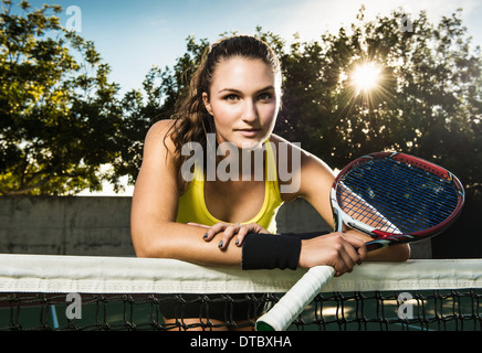 Female tennis player holding racket leaning on net - Stock Photo